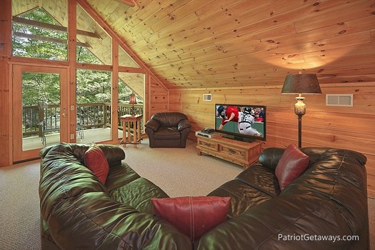 large sectional couch and tv in lofted bedroom at a moment in time a 2 bedroom cabin rental located in gatlinburg