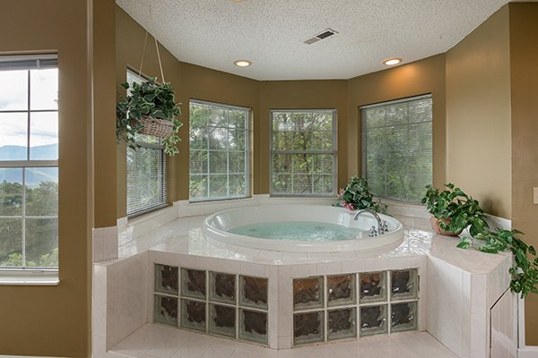 In room jacuzzi tub surrounded by windows at Castle on the Hill, a 2-bedroom cabin rental located in Gatlinburg