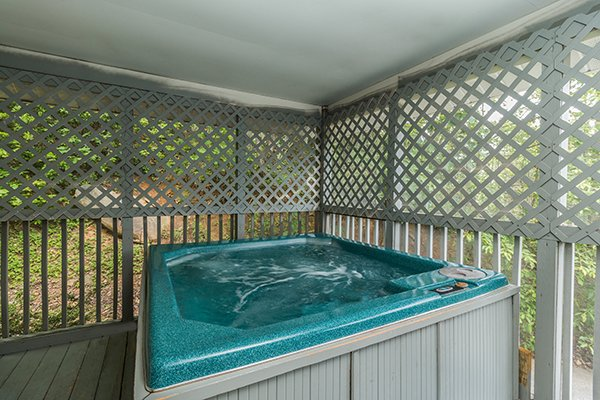 Hot tub on a covered deck surrounded by lattice fencing at Castle on the Hill, a 2-bedroom cabin rental located in Gatlinburg
