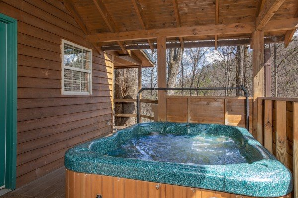 Hot tub on a covered deck at Hideaway, a 1 bedroom cabin rental located in Pigeon Forge