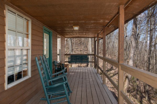 Front deck with rocking chairs and a swing at Hideaway, a 1 bedroom cabin rental located in Pigeon Forge
