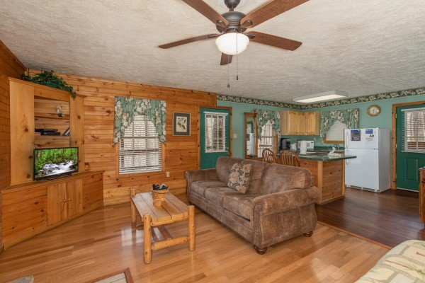 Living room with sofa, TV, and adjacent kitchen at Hideaway, a 1 bedroom cabin rental located in Pigeon Forge