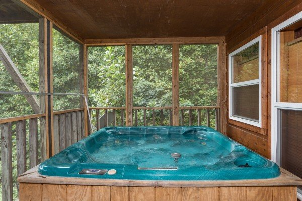 Hot tub on a screened in porch at Paradise View, a 1 bedroom cabin rental located in Pigeon Forge