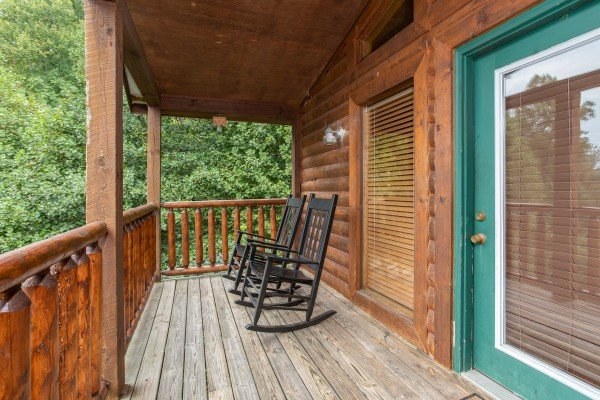 Rocking chairs on a covered deck at Paradise View, a 1 bedroom cabin rental located in Pigeon Forge