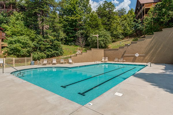outdoor pool and lounge chairs in resort setting at alpine sunset thrill a 1 bedroom cabin rental located in pigeon forge