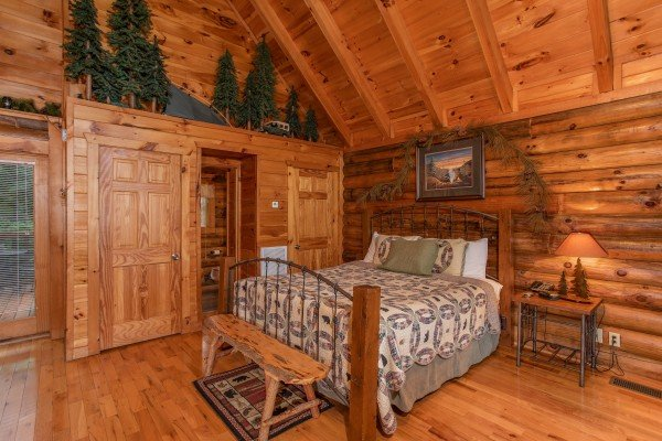 bedroom with queen bed and wooden bench at alpine sunset thrill a 1 bedroom cabin rental located in pigeon forge