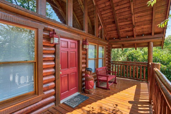 front covered porch with red bench at alpine sunset thrill a 1 bedroom cabin rental located in pigeon forge