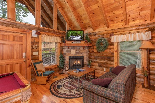 living room with a television and stone fireplace at alpine sunset thrill a 1 bedroom cabin rental located in pigeon forge
