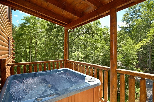 Covered deck with hot tub at Pool House, a 2 bedroom cabin rental located in Gatlinburg