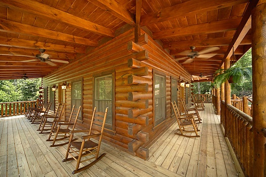 Front and side decks with rocking chairs at Pool House, a 2 bedroom cabin rental located in Gatlinburg