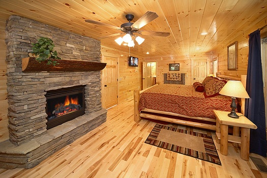 King bedroom with fireplace at Pool House, a 2 bedroom cabin rental located in Gatlinburg