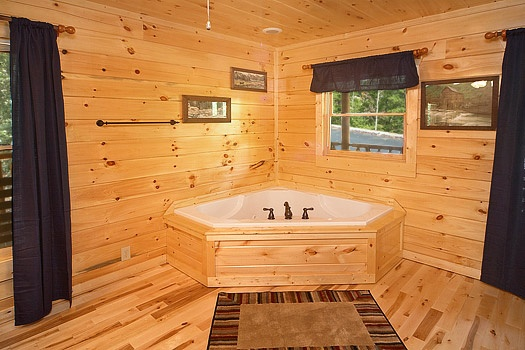 king bedroom with jacuzzi tub at pool house a 2 bedroom cabin rental located in gatlinburg