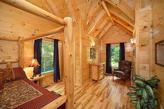 Second level queen bed with sitting area at Pool House, a 2 bedroom cabin rental located in Gatlinburg