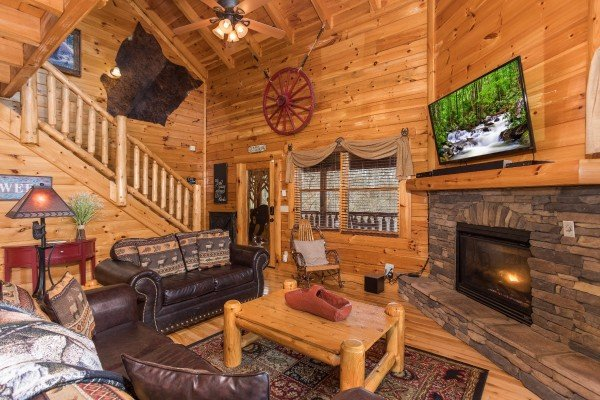 Living room with fireplace, TV, and front entry at Mountain View Meadows, a 3 bedroom cabin rental located in Pigeon Forge