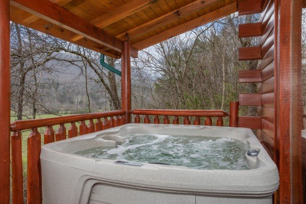 Hot tub on a covered deck at Mountain View Meadows, a 3 bedroom cabin rental located in Pigeon Forge