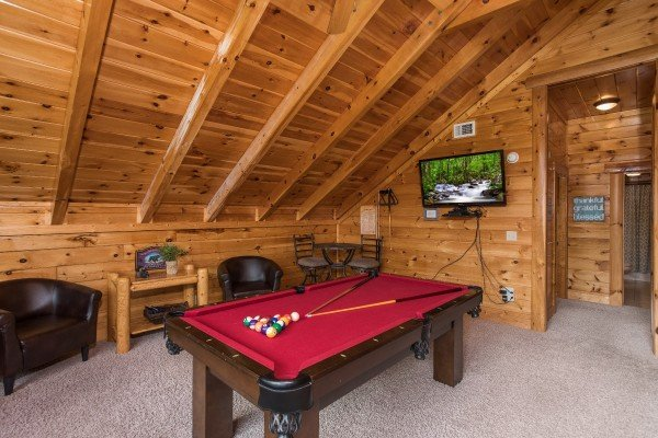 Pool table and television at Mountain View Meadows, a 3 bedroom cabin rental located in Pigeon Forge
