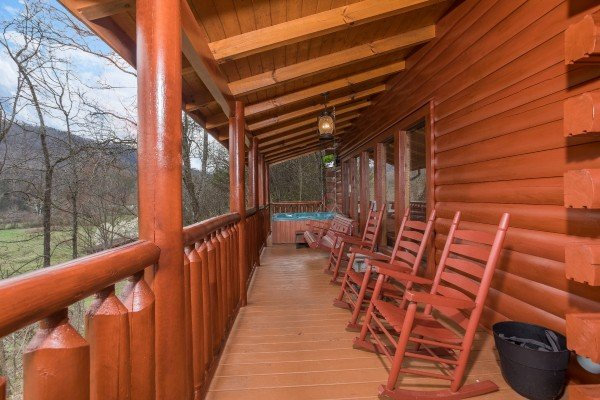 Covered porch with rocking chairs and hot tub at Mountain View Meadows, a 3 bedroom cabin rental located in Pigeon Forge