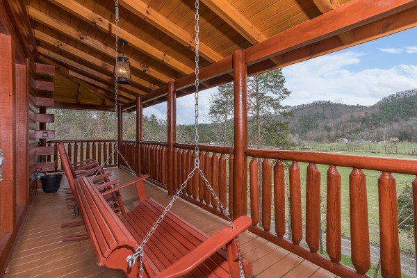 Porch swing on a covered porch at Mountain View Meadows, a 3 bedroom cabin rental located in Pigeon Forge