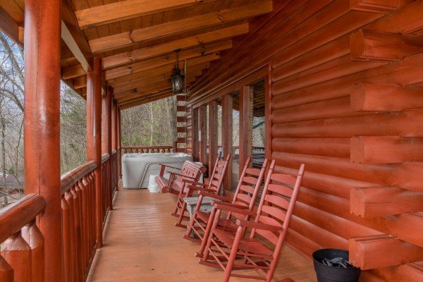 Rocking chairs and hot tub on a covered deck at Mountain View Meadows, a 3 bedroom cabin rental located in Pigeon Forge