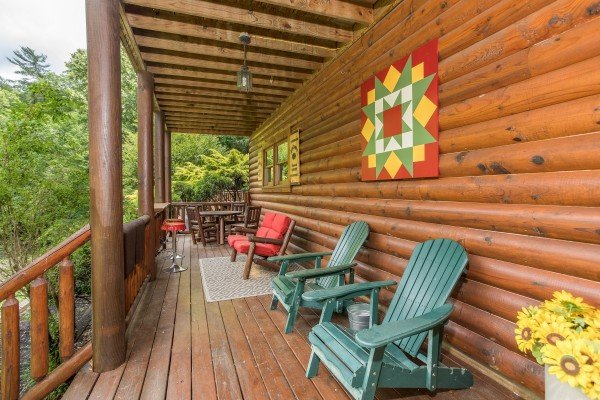 Adirondack chairs on the covered deck at Creekside Lodge, a 6-bedroom cabin rental located in Pigeon Forge