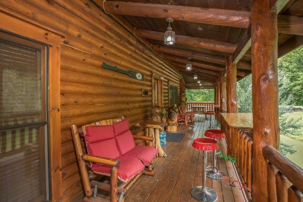 Plenty of seating and bar top tables on the covered deck at Creekside Lodge, a 6-bedroom cabin rental located in Pigeon Forge