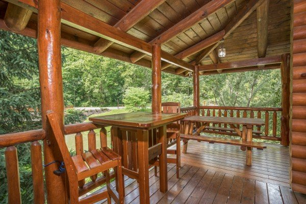 Picnic table and high top table for two on the covered deck at Creekside Lodge, a 6-bedroom cabin rental located in Pigeon Forge