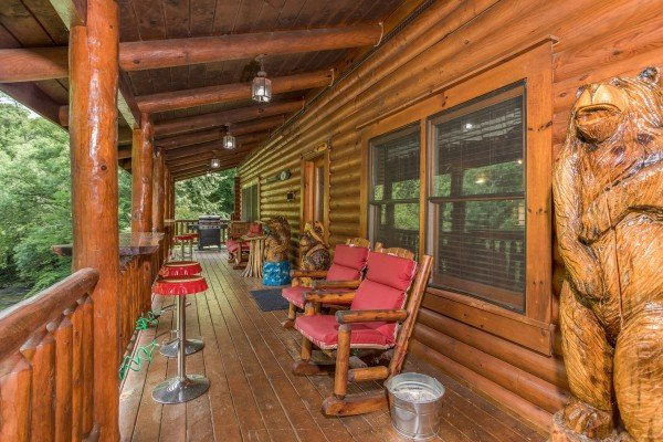 Covered deck with rocking chairs and bar stools at Creekside Lodge, a 6-bedroom cabin rental located in Pigeon Forge
