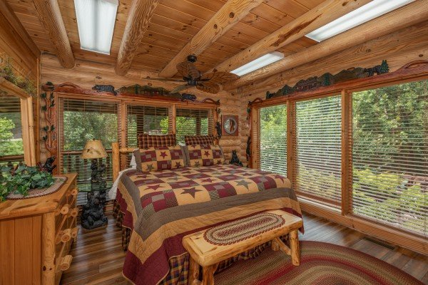 Bedroom with a king bed, dresser, and bench at Creekside Lodge, a 6-bedroom cabin rental located in Pigeon Forge