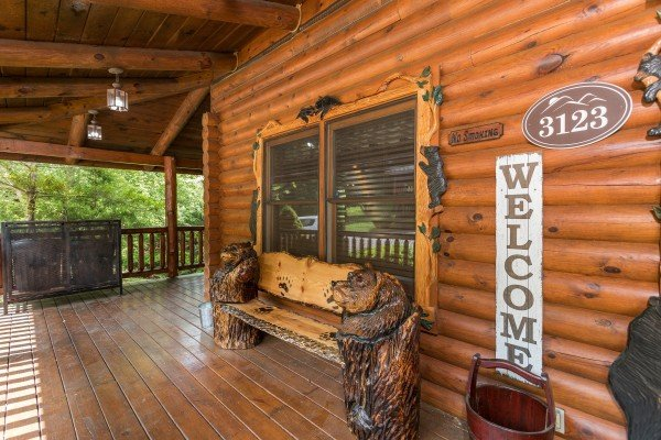 Front porch with custom log bench at at Creekside Lodge, a 6-bedroom cabin rental located in Pigeon Forge