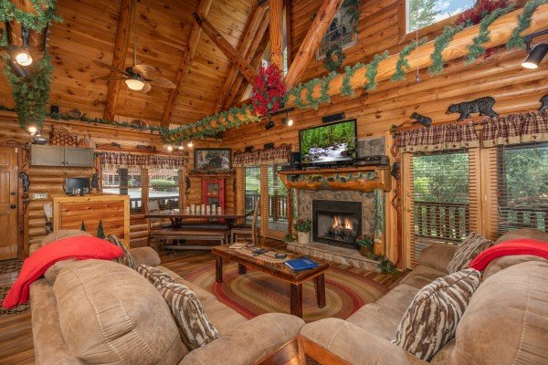 Vaulted living room with fireplace and TV at Creekside Lodge, a 6-bedroom cabin rental located in Pigeon Forge