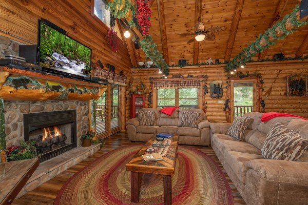 Two sofas, coffee table, fireplace, and TV in a living room at Creekside Lodge, a 6-bedroom cabin rental located in Pigeon Forge