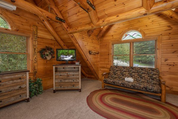 Futon and dresser with a TV in the loft at Creekside Lodge, a 6-bedroom cabin rental located in Pigeon Forge