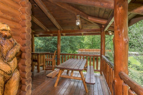 Picnic table on the covered deck at Creekside Lodge, a 6-bedroom cabin rental located in Pigeon Forge