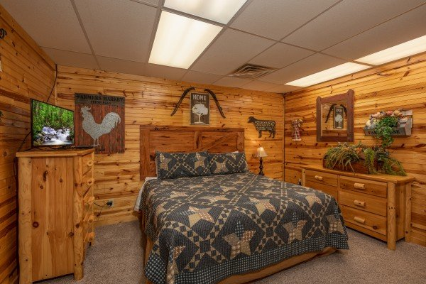 King bed, two dressers, and a TV in a bedroom at Creekside Lodge, a 6-bedroom cabin rental located in Pigeon Forge