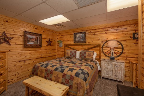 Queen bed, bench, and side table at Creekside Lodge, a 6-bedroom cabin rental located in Pigeon Forge