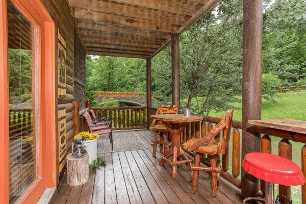 Dining table for two and chairs on the lower deck at Granny's Creekside Cabin, a 6-bedroom cabin rental located in Pigeon Forge