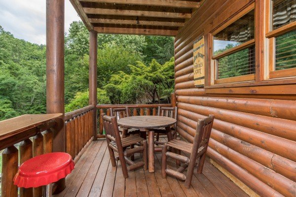 Dining space for four and two bar stools on the lower deck at Granny's Creekside Cabin, a 6-bedroom cabin rental located in Pigeon Forge
