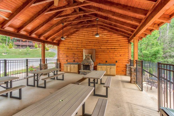 BBQ and picnic tables in the pavilion at Granny's Creekside Cabin, a 6-bedroom cabin rental located in Pigeon Forge