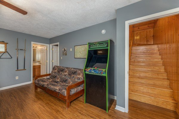 Futon and arcade game at Wildlife Retreat, a 3 bedroom cabin rental located in Pigeon Forge