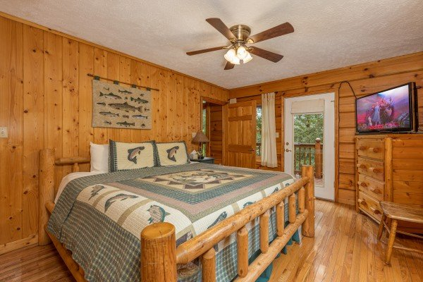 Bedroom with a king bed, dresser, TV, and deck access at Wildlife Retreat, a 3 bedroom cabin rental located in Pigeon Forge