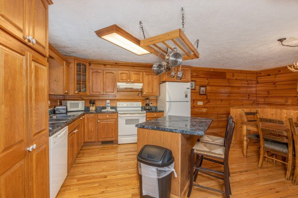 Kitchen with white appliances and a breakfast bar at Wildlife Retreat, a 3 bedroom cabin rental located in Pigeon Forge