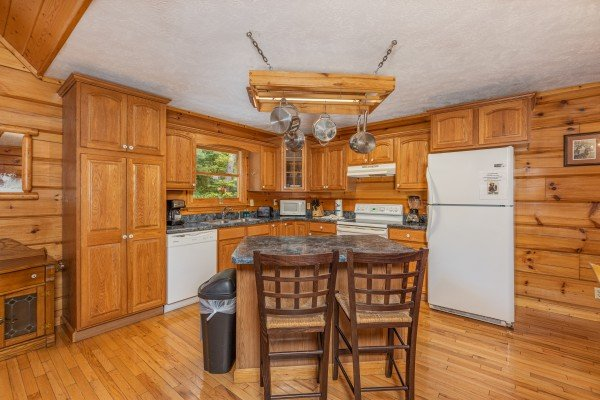 Breakfast bar for two in a kitchen with white appliances at Wildlife Retreat, a 3 bedroom cabin rental located in Pigeon Forge