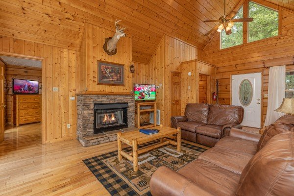 Sofa, loveseat, fireplace, and TV in a living room at Wildlife Retreat, a 3 bedroom cabin rental located in Pigeon Forge