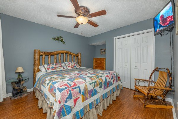 Bedroom with a night stand, chair, and TV at Wildlife Retreat, a 3 bedroom cabin rental located in Pigeon Forge