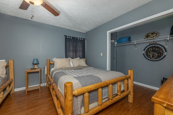 Bedroom with two beds, dresser, table, and lamp at Wildlife Retreat, a 3 bedroom cabin rental located in Pigeon Forge