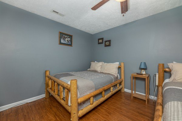 Bedroom with two beds, a table, and lamp at Wildlife Retreat, a 3 bedroom cabin rental located in Pigeon Forge