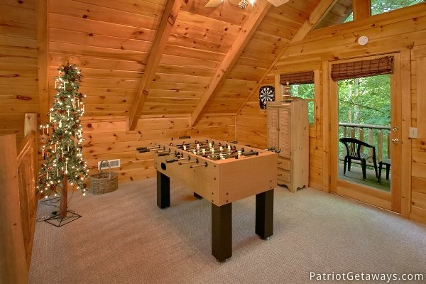 Foosball table and dart board in the lofted game room at A Bear's View, a 1 bedroom cabin rental located in Gatlinburg