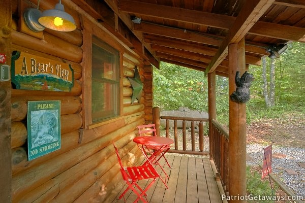 Bistro table and chairs on the front porch at A Bear's View, a 1 bedroom cabin rental located in Gatlinburg