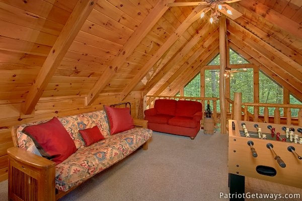 Lofted game room seating and futon at A Bear's View, a 1 bedroom cabin rental located in Gatlinburg