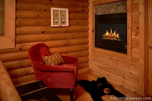 Comfy reading chair next to the fireplace in the bedroom at A Bear's View, a 1 bedroom cabin rental located in Gatlinburg